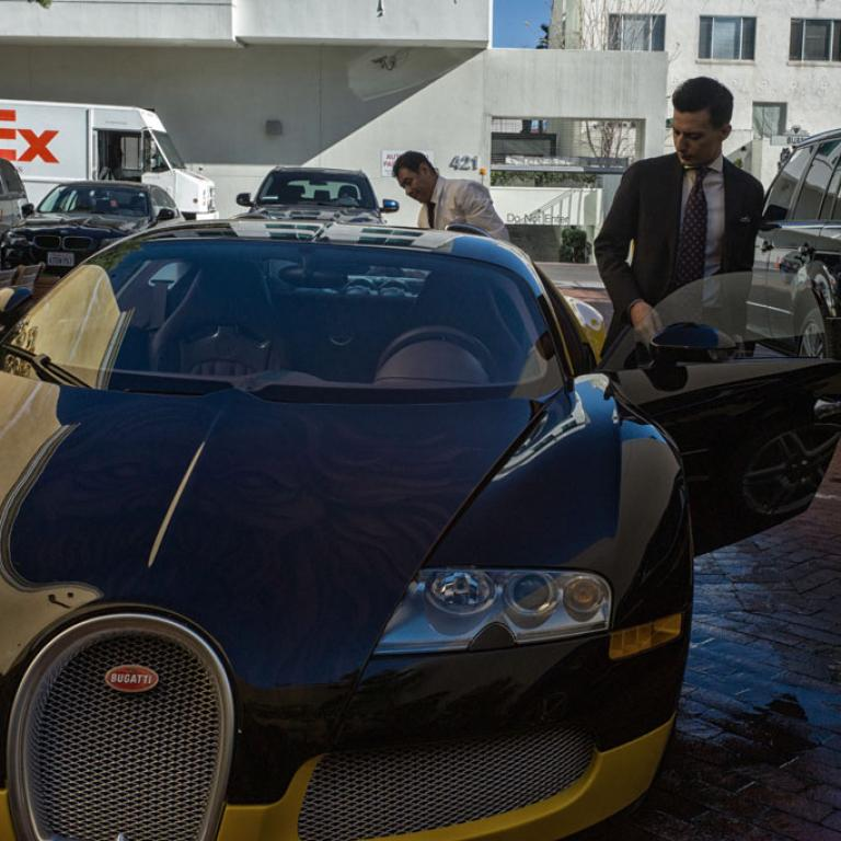 A man gets into a Bugatti sports car behind the House of Bijan, said to be the most expensive clothing store in the US.  (Sim Chi Yin/VII/GlobalPost)