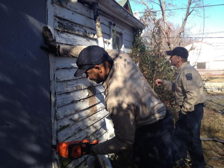 The Topeka Rescue Mission accompanies the police as they search and seal off abandoned homes that have been being used for shelter by the homeless. (Nichole Sobecki/GlobalPost)