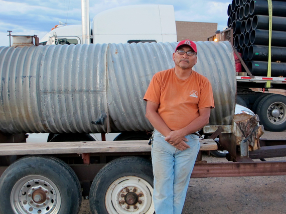 Edward Bennett, a Navajo rancher, leans against his water tank at the Shell Gas Station in Page, Arizona. With no running water for his family or his livestock, Bennett fills up the tank at least twice a day. (Photo by Charlotte Weiner/GroundTruth)