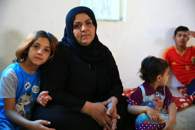 Dunya's mother sits with her other children in her family home.  (Tracey Shelton/GlobalPost)