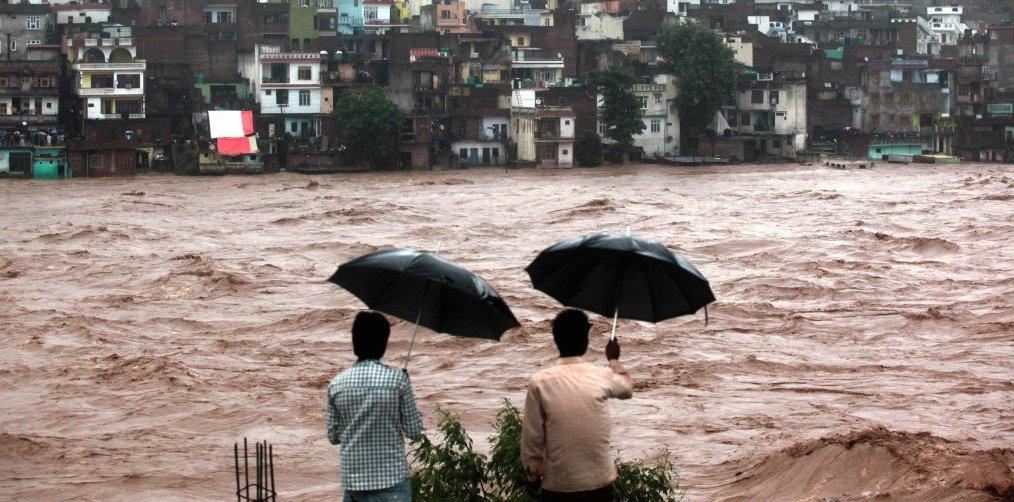 men with umbrellas watch muddy river