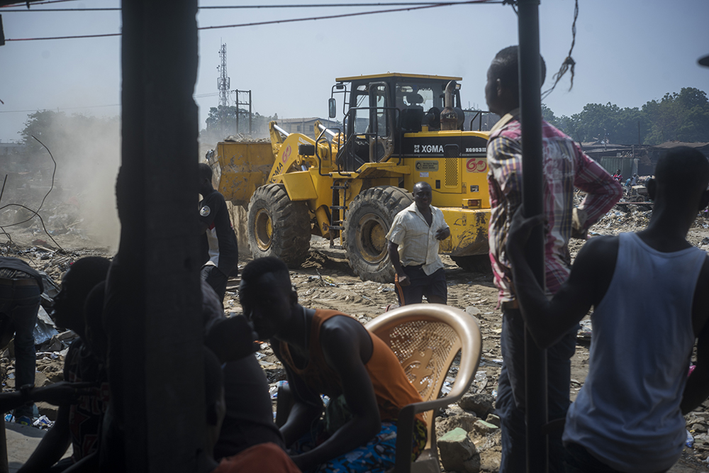 On a Saturday morning in June 2015, the Accra Metropolitan Assembly (AMA) demolished the homes of over 20,000 people in Agbogbloshie to access the area, dredge the waterways and avoid the floods that affect the city every year during the rainy season. Awal and his friends watch from a distance.