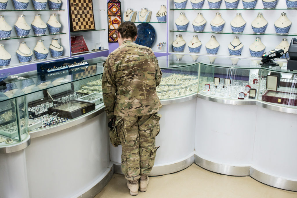 A soldier at Kandahar Airfield shops for jewelry on the 10-year-old store's last day of business. (Photo by Ben Brody)