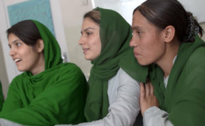 (From left) Aziza, Yalda and Negina listen to Shakira talking about her father's garden. He brought watermelon to the school to celebrate the community college, and Shakira distributed it to students and teachers. (Photo by Beth Murphy)