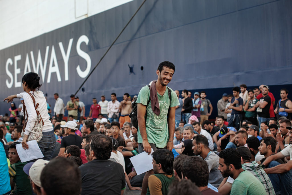 Asaad Sieo, a Syrian military defector, smiled in relief after receiving his legal documents in Lesvos, Greece . Sieo waited in line for three days in order to get processed and receive documents. Many refugees wait for multiple days in line in order to receive legal documents allowing them to travel further into Greece.
