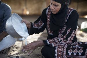 Um Hussein al-Mazana mixes fresh camel milk into a glass of traditional Bedouin tea in Jordan's Wadi Rum desert on August 6, 2015.
