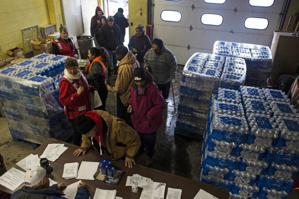 Local residents wait in line to pick up Brita water filters at the Flint Fire Department in downtown Flint on January 15, 2016. Following the declaration for a state of emergency, local fire stations began acting as water resource centers, where residents could pick up water filters, lead testing kits and cases of bottled water. (Brittany Greeson/GroundTruth)