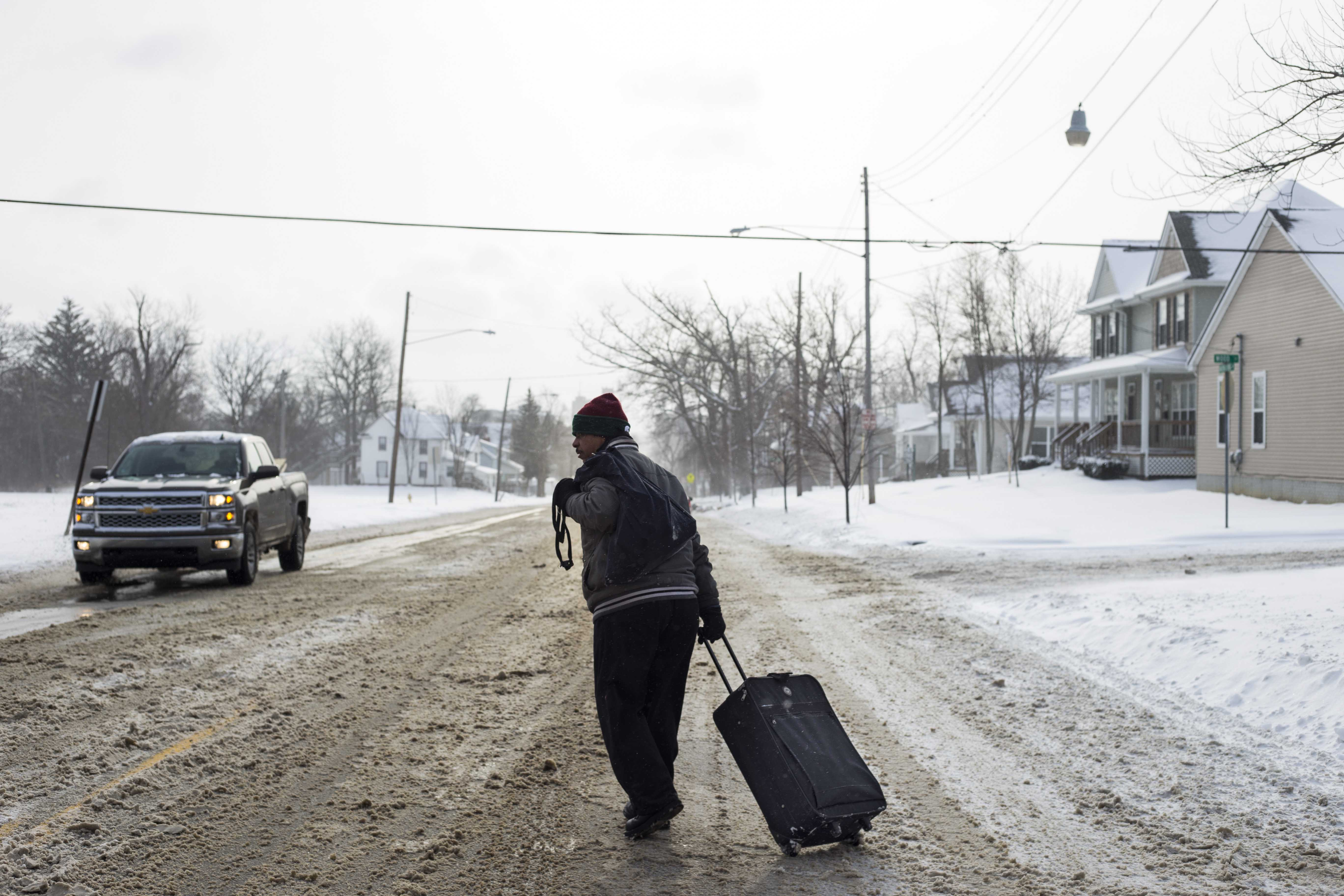 A man who gave his name as Chester braves below freezing temperatures to drag a suitcase full of bottled water from Firehouse #3, where water was being handed out to residents by American Red Cross workers, to catch a bus back to his family's home in Flint on January 12, 2016. Many resident's in Flint lack viable transit options which has left them resorting to the city's bus system to get heavy cases of bottled water. (Brittany Greeson/GroundTruth)
