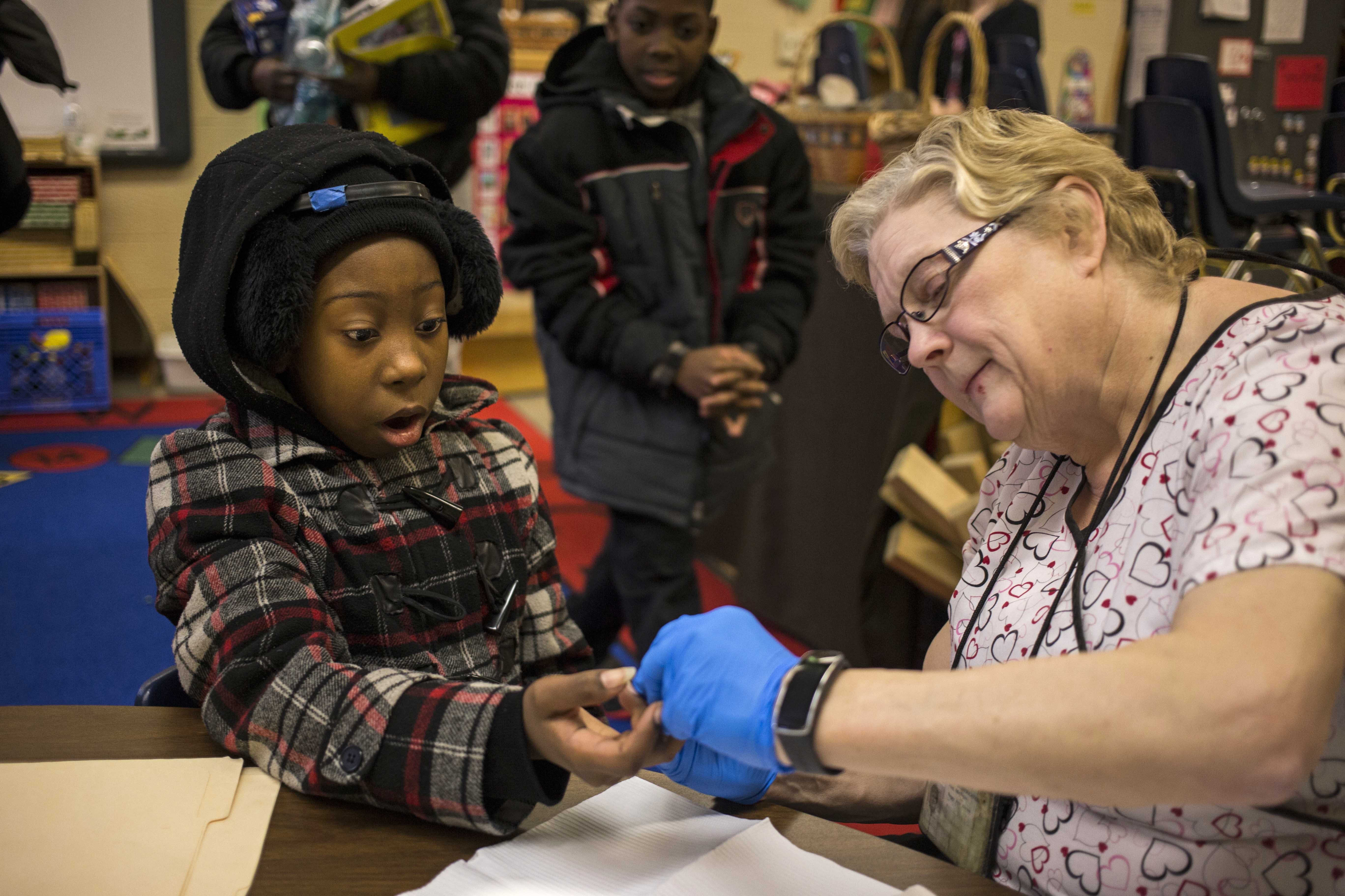 Ti'Nisha Norman, 11, get's her blood lead levels tested at Freeman Elementary School's Family Fun and Lead Testing night on January 12, 2016. (Brittany Greeson/GroundTruth)