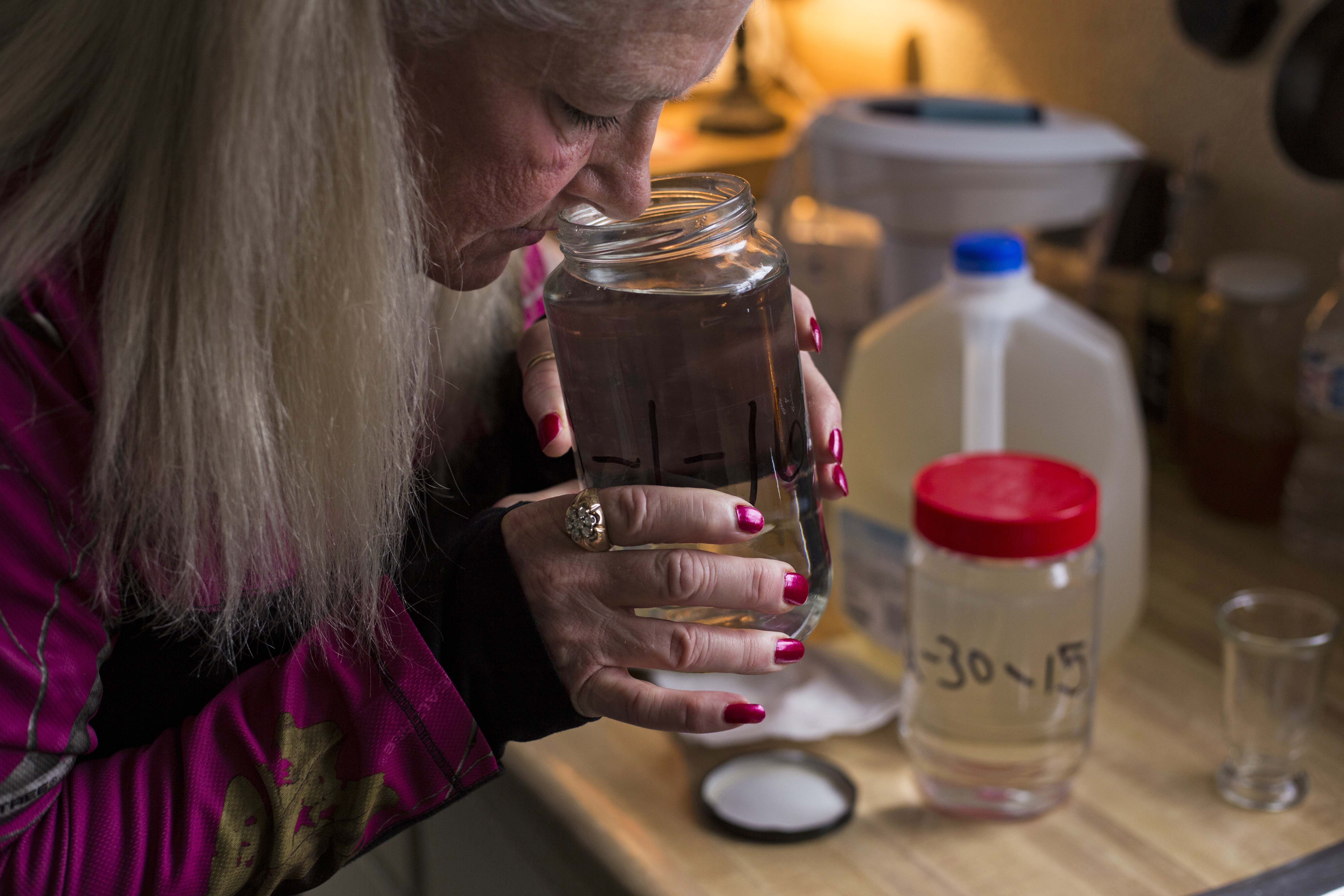 Gladyes Williamson smells a jar of water she collected from her tap earlier that month on January 13, 2016. Williamson has been recording her struggle with Flint's water crisis since the city switched water sources in early 2014. (Brittany Greeson/GroundTruth)