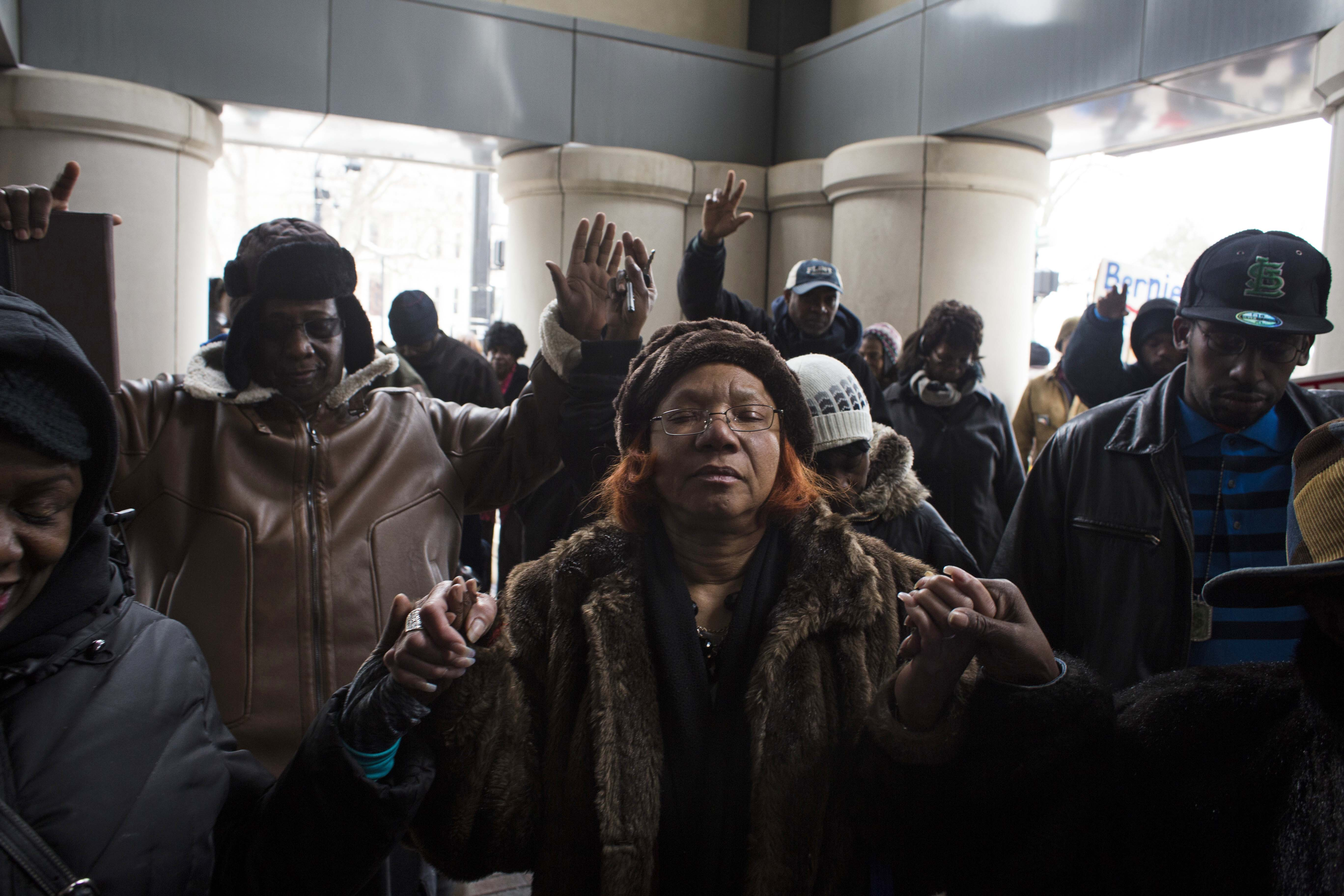 Earlene Love, 64, prays alongside her peers as protestors gather outside the Romney building, which houses the office of Governor Rick Snyder, on January 14, 2016. (Brittany Greeson/GroundTruth)