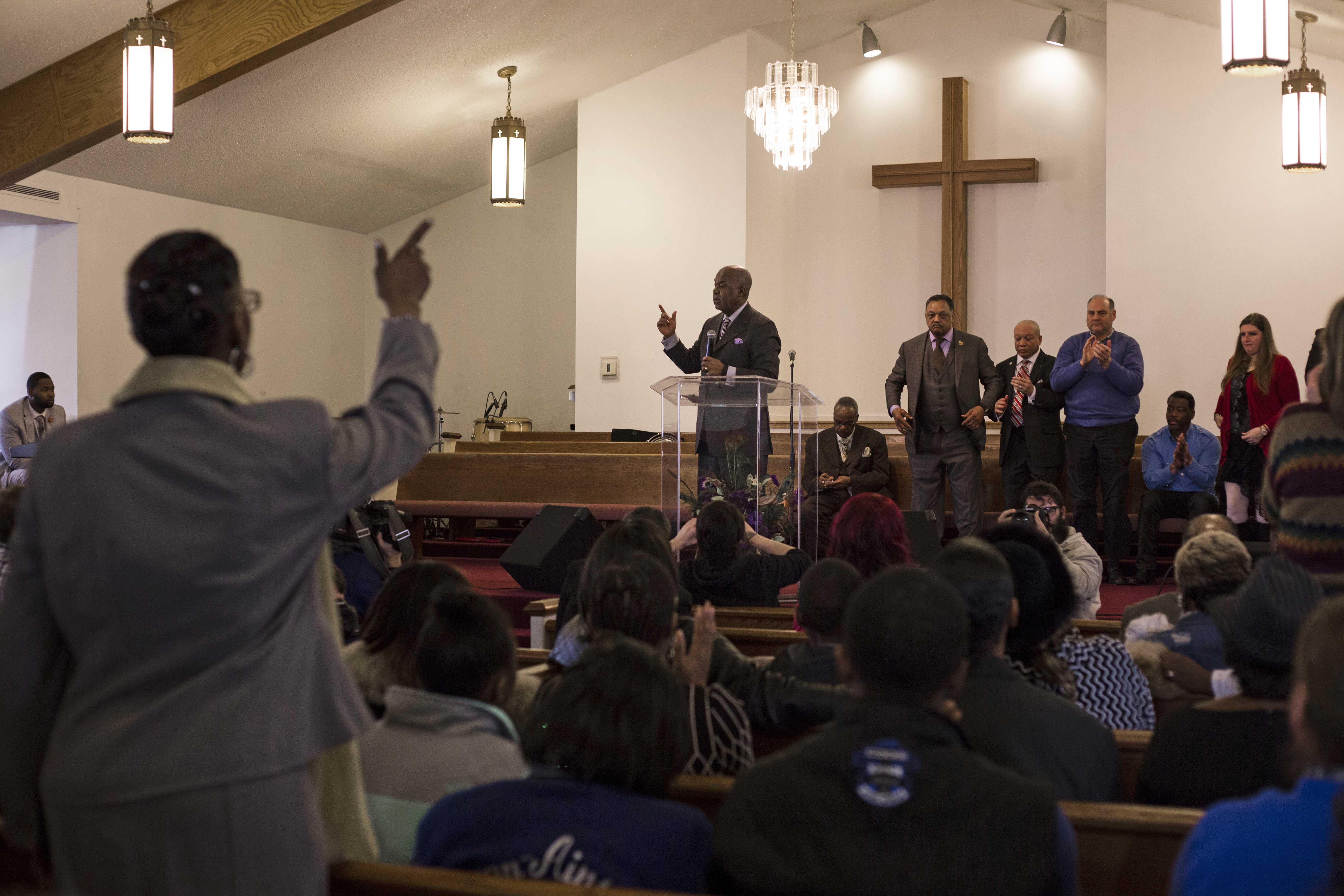 Resident's rise in agreement while attending a service discussing Flint's ongoing water crisis that invited civil right's activist Jesse Jackson, government leaders and local leaders at Heavenly Host Baptist Church in Flint's north side on January 17, 2016. (Brittany Greeson/GroundTruth)