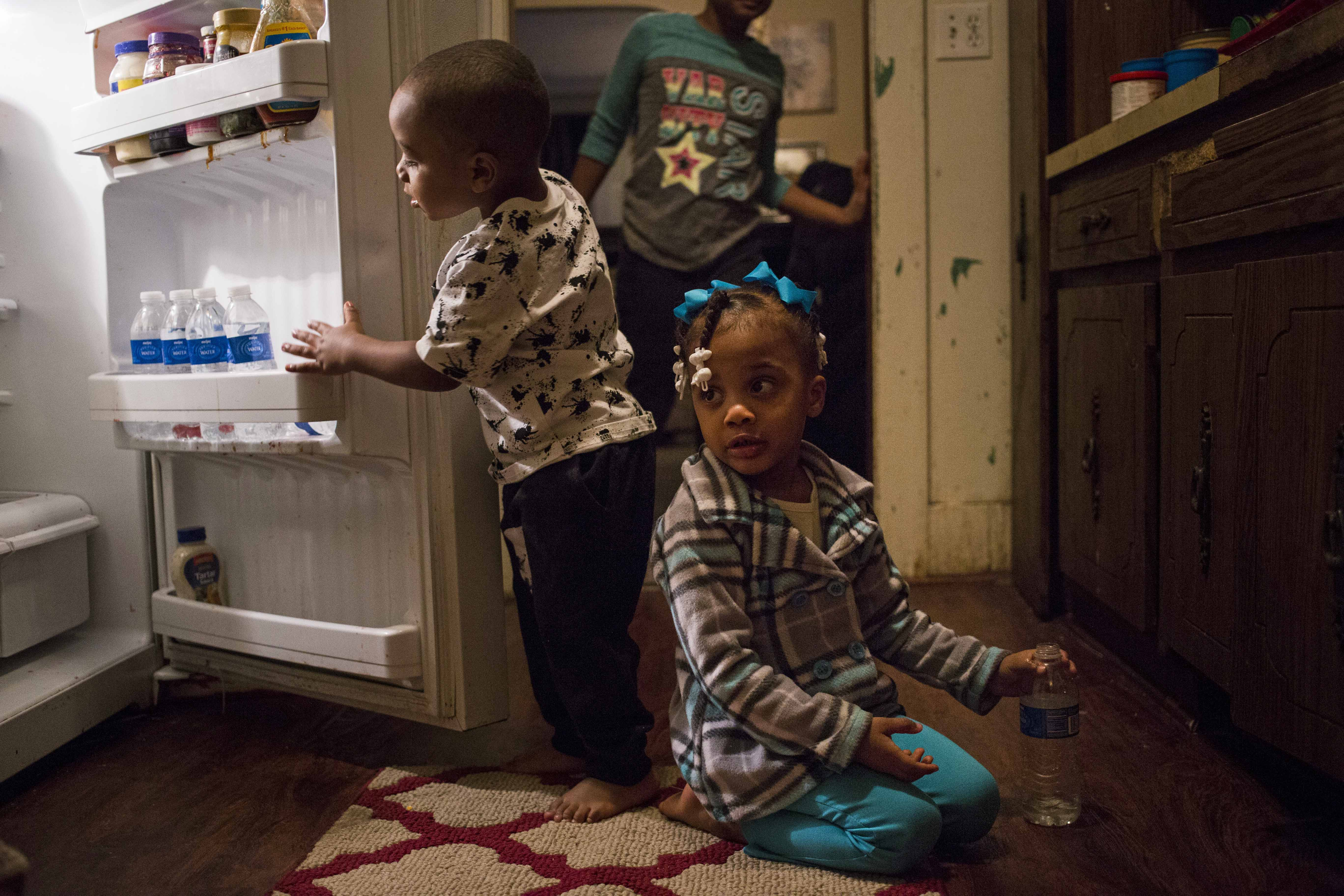 Journey Jones, 3, sits on the kitchen floor in her family's home as her brother Iveon Jones, 2, reaches for a bottled water. The pair are two of six children living in the home, all of whom have had elevated levels of lead in their blood. (Brittany Greeson/GroundTruth)