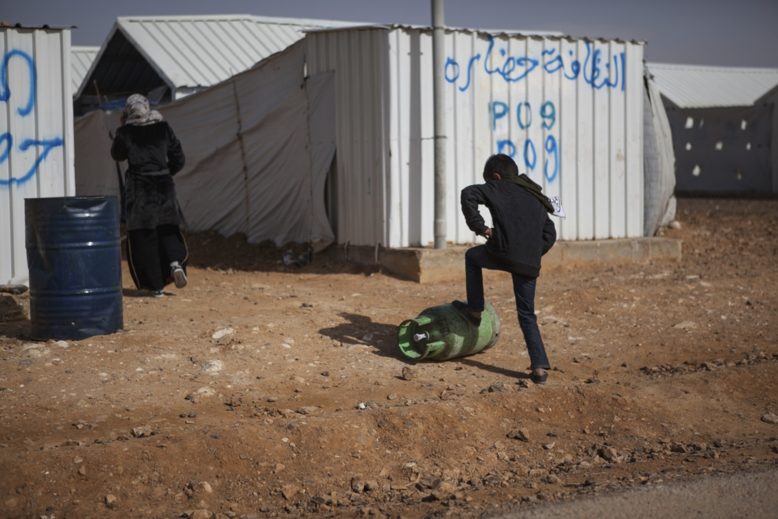 A young boy pushes a gas tank up a street in Azraq refugee camp, January 19, 2016. (Christopher Lee/GroundTruth)