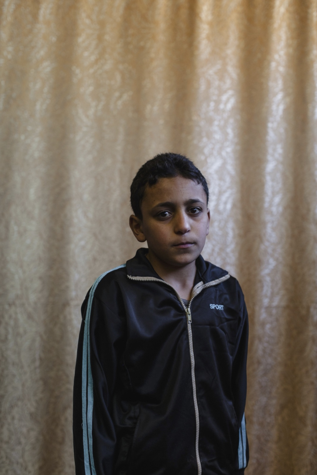 Mohamad Maher, 12, a Syrian refugee from Daraa, has been living in Amman, Jordan, for three years poses for a portrait in the community center room at Dar Al-Ihsan For Orphans. His mother died during childbirth. Dar Al-Ihsan For Orphans was started in April 2014 and provides education, housing, food vouchers, medical insurance and other services to the most vulnerable cases. (Christopher Lee/GroundTruth)