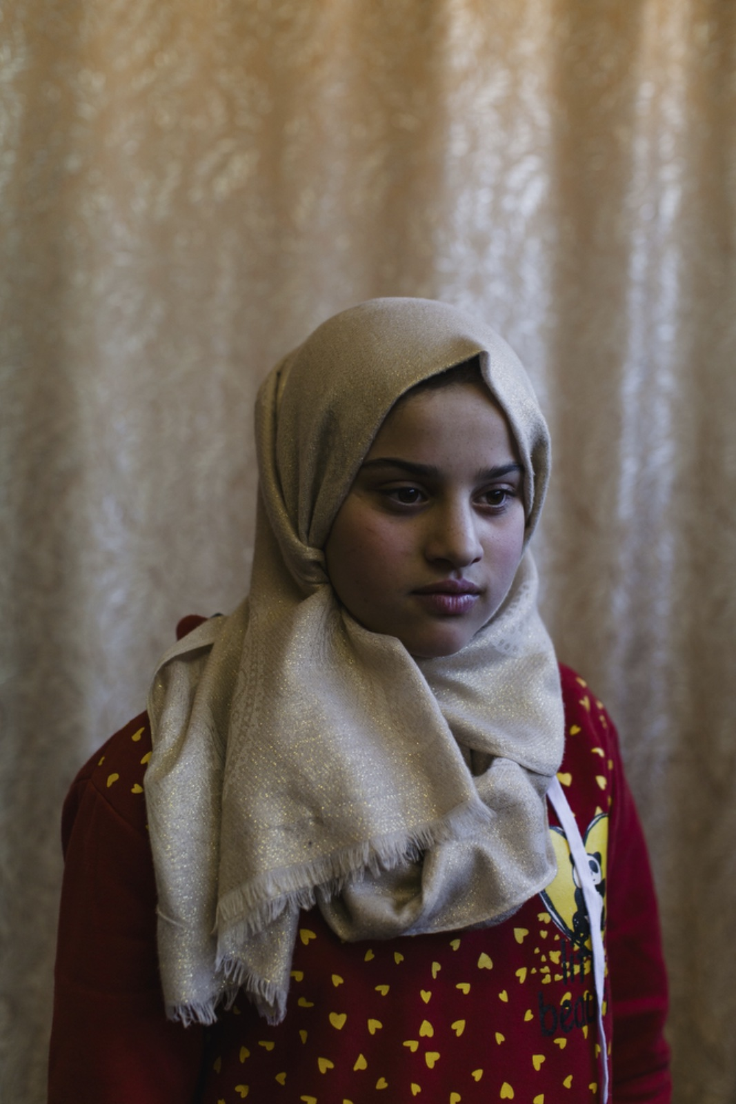 Asmaa Ayob, 13, a Syrian refugee from Daraa has been living in Amman, Jordan, for four years, poses for a portrait in the community center of Dar Al-Ihsan For Orphans, an organization that provides aid to orphaned children. Her father was killed during shelling in Syria. (Christopher Lee/GroundTruth)