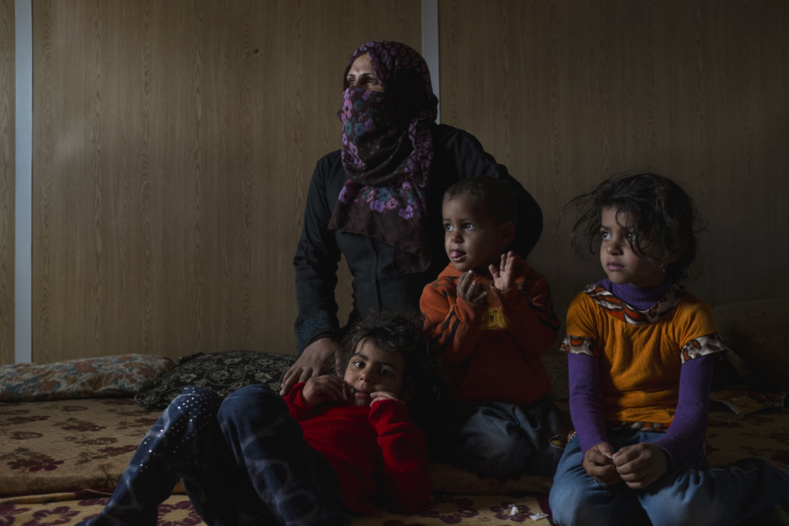 Ammeh Salah (center left), 29, from Damascus, sits with her children Jhazel (right), 6, Mohamed (center right), 3, and Arreeg (left), 5, in their caravan in the Zaatari refugee camp. Ammeh, a single mother, whose husband disappeared in Syria, supports her five children alone. The family has been living in Zaatari for four years. (Christopher Lee/GroundTruth)