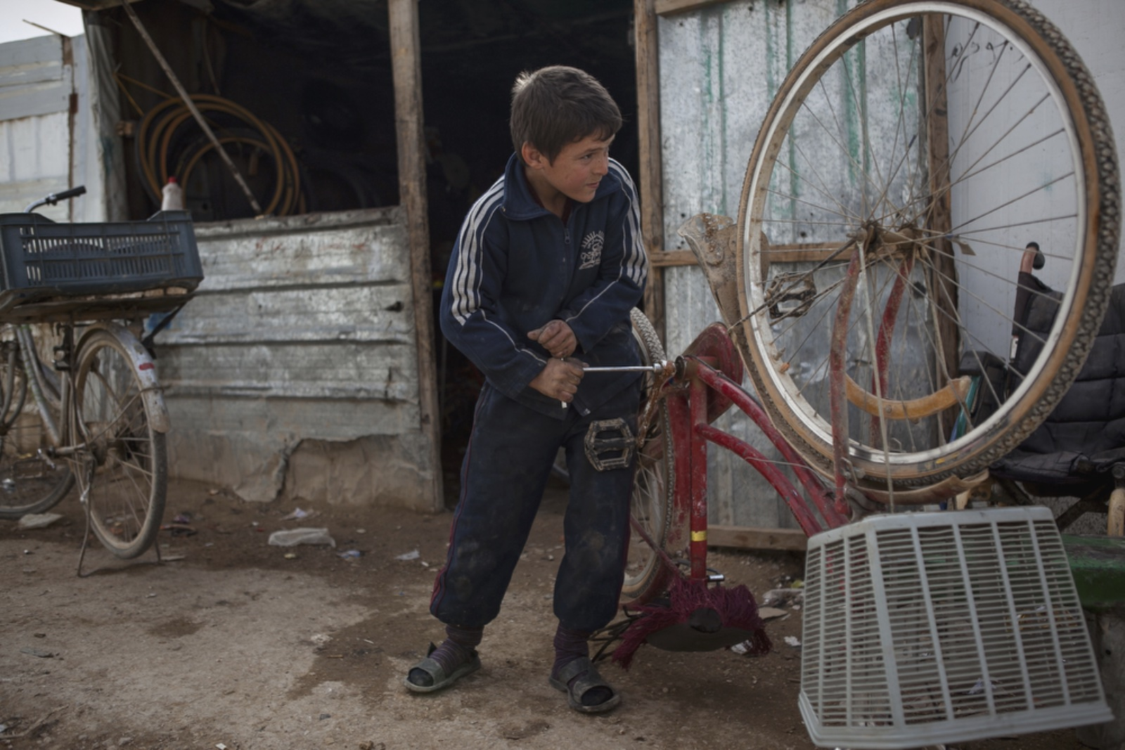 Ebraham Alatmia, 11, a Syrian refugee from Daraa, fixes a bicycle in a makeshift bike shop where he works in the main marketplace of Zaatari. (Christopher Lee/GroundTruth)
