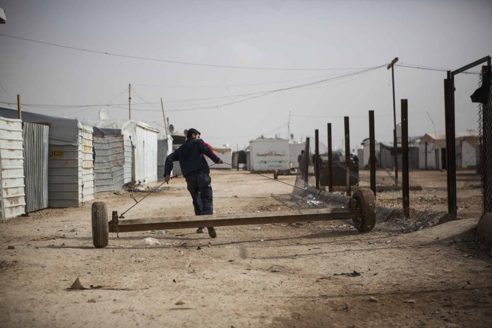 A Syrian refugee pulls a trailer that is used to haul large objects, including a whole caravan, down a street in Zaatari refugee camp on January 18, 2016. (Christopher Lee/GroundTruth)