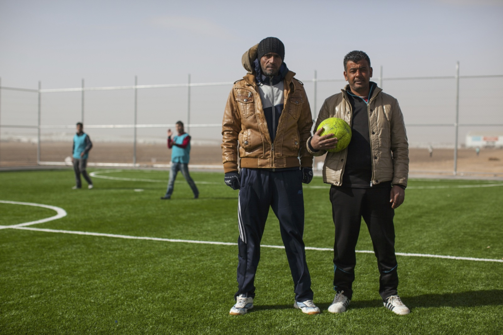 Mousa Hassan (left), 35, and Mamon Gabao (right), 37, both Syrian refugees from Daraa and coaches trained by the Premier League for the soccer program, pose for a portrait during a soccer match on one of the pitches provided by World Vision at Azraq refugee camp, January 19, 2016. Recreation soccer teams are formed to provide a better quality of life for the children living in the camp. (Christopher Lee/GroundTruth)