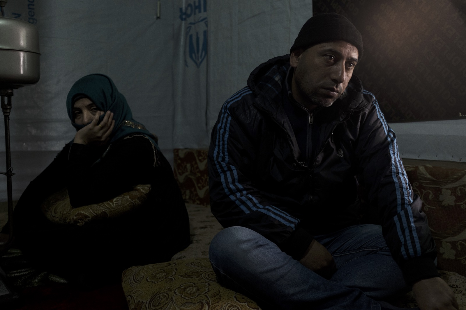 Abu Mohammad (right), sits with his wife, Um Mohammad (left) in their improvised tented settlement in the Bekaa Valley. Out of fear for their teenaged daughter's safety, Abu Mohammad arranged for her to be married at the age of 13. But their daughter's husband turned out to be abusive, and she is not allowed to move or live freely. (Christopher Lee/GroundTruth)