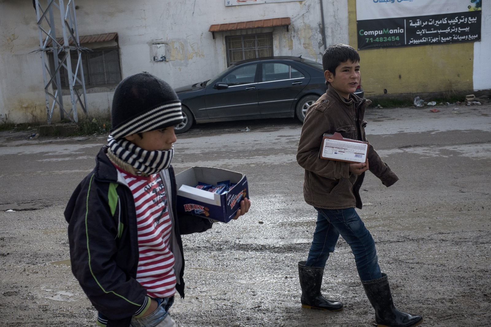 Mahmut (left), 8, a Syrian refugee from Homs, walks to the main street to sell biscuits with his brother, Khaled (right), 12, in the Bekaa Valley. (Christopher Lee/GroundTruth)