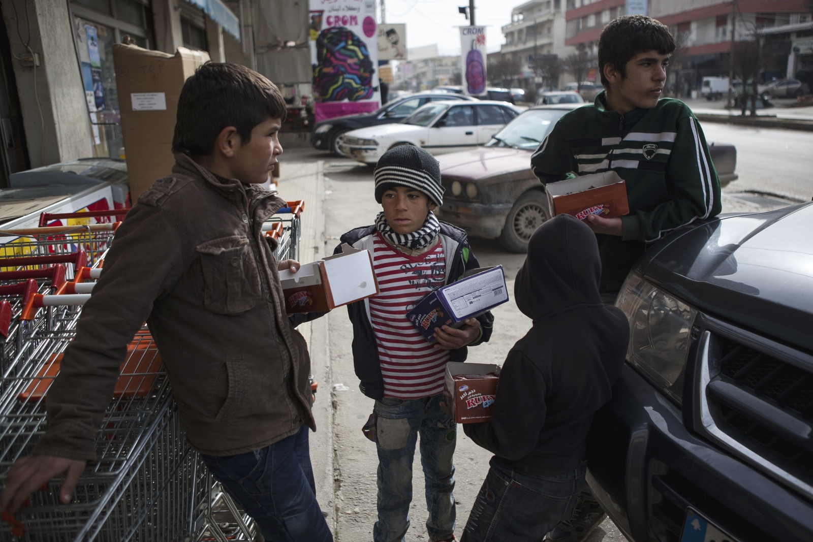 Khaled (left), 12, Mahmut (center), 8, and Ahmed (right), 15, brothers and refugees from Homs, wait for customers to come out of a grocery story while selling biscuits in the Bekaa Valley while selling biscuits. (Christopher Lee/GroundTruth)