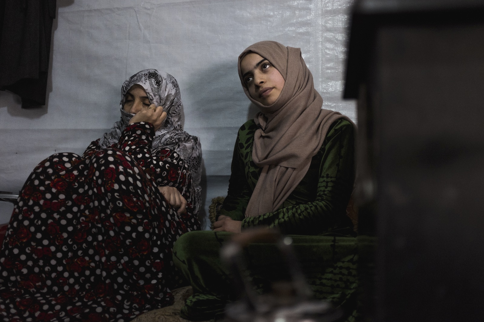 Batoul (right), 15, sits with her mother, Um Mohammad (left), in their improvised tent settlement. Batoul's family got her married off when she was 13 out of fear for her safety. However, her husband has been physically and emotionally abusive and does not allow her any freedoms. (Christopher Lee/GroundTruth)