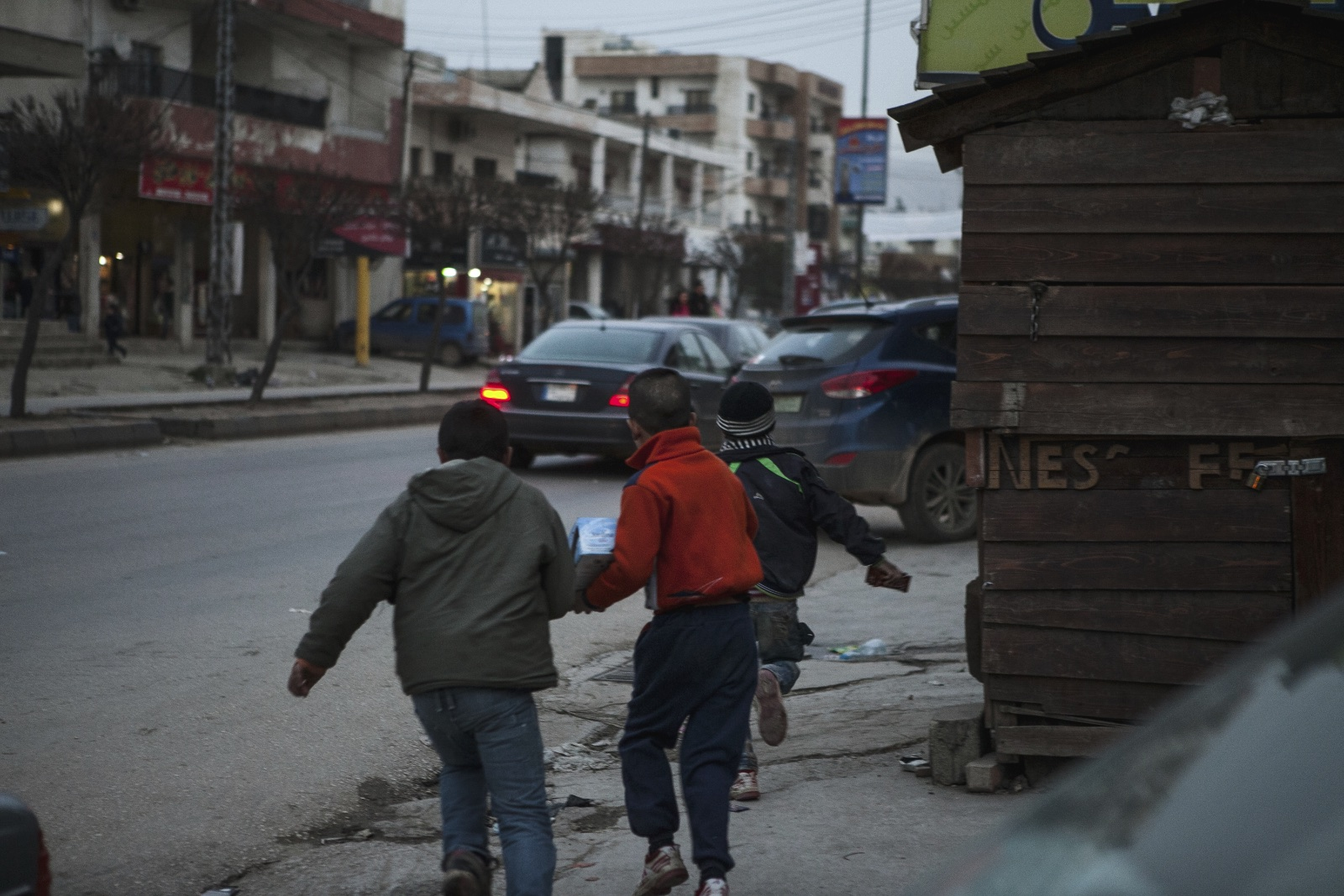 Syrian refugee children run away from a Lebanese store owner who chased them from his property in the Bekaa Valley. (Christopher Lee/GroundTruth)