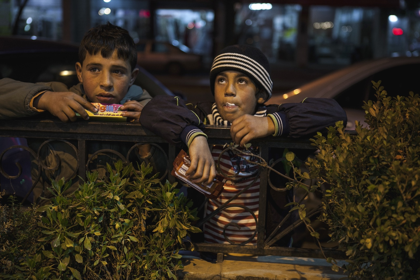 Mahmut (right), 8, a Syrian refugee from Homs, and another child waited for people to come out of a restaurant in the Bekaa Valley where they sell biscuits. (Christopher Lee/GroundTruth)