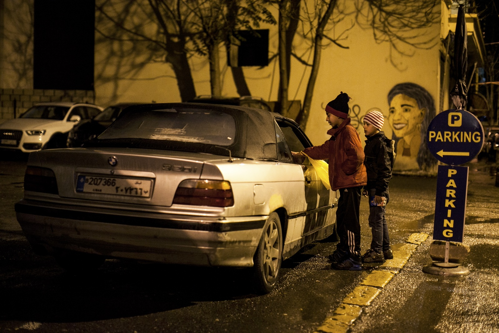 Nasar (left), 11, and his brother Ali, 9, Syrian refugees from Aleppo, approach a car near Hamra Street in Beirut, attempting to sell packages of peanuts. Among the 1.8 million Syrian refugees in Lebanon, women and children remain the most vulnerable. (Christopher Lee/GroundTruth)