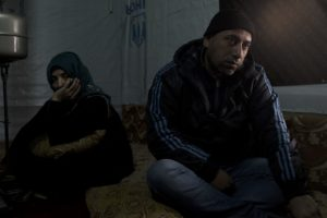 Abu Mohammad (right), sat with his wife, Um Mohammad (left) in their improvised tented settlement in the Bekaa Valley. Out of fear for their teenaged daughter's safety, the Abu Mohammad, arranged her to be married at the age of 13.   Unfortunately, Batoul, the daughter, is suffering from domestic violence and is not allowed to move or live freely. (Photo by Christopher Lee/GroundTruth)