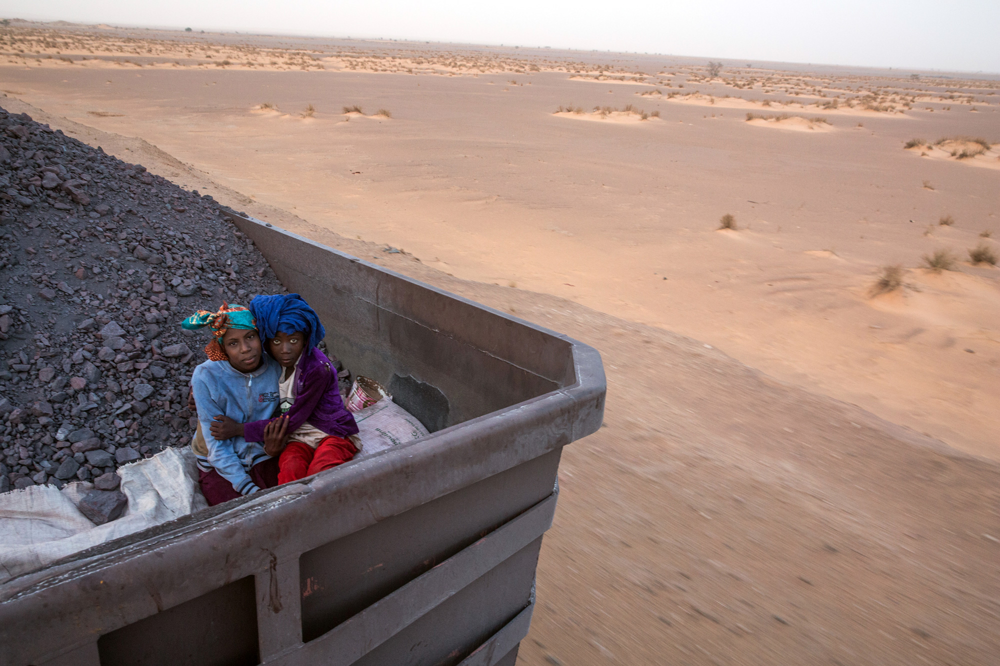 Two sisters pose for a portrait while traveling with their family (not pictured) on the cargo train that crosses the Sahara desert on October 1, 2015. (George Popescu/GroundTruth)