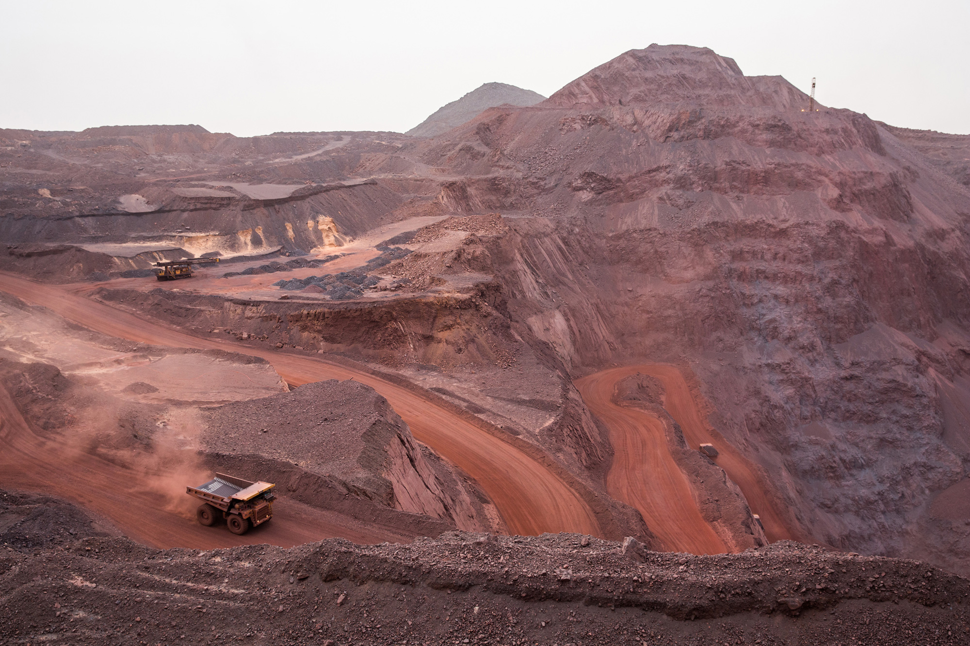 Trucks transporting iron ore are seen at one of the Zouérat open-cast mines. After it is extracted, the iron ore is loaded and transported on the freight trains that travel about 435 miles to the coast, and can be as long as 1.5 miles, according to Societe Nationale Industrielle et Miniere (SNIM), the Mauritanian government mining company. (George Popescu/GroundTruth)