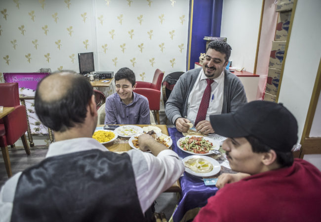 Salloura employees, including head waiter Abu Yazan (top right) sit down for a meal. (Photo by Joris van Gennip/GroundTruth)