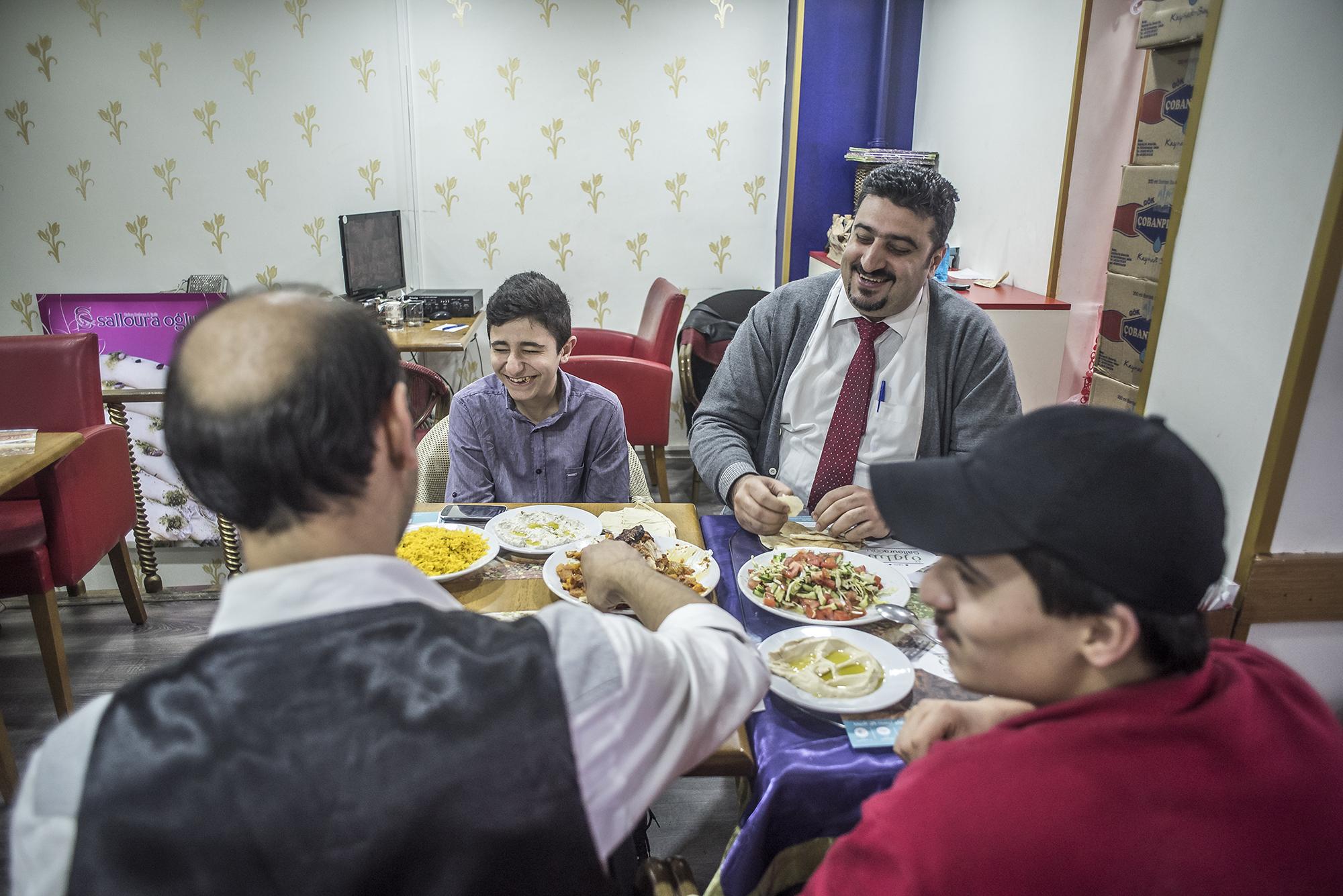 Salloura employees, including head waiter Abu Yazan (top right) sit down for a meal. (Photo by Joris van Gennip/GroundTruth)