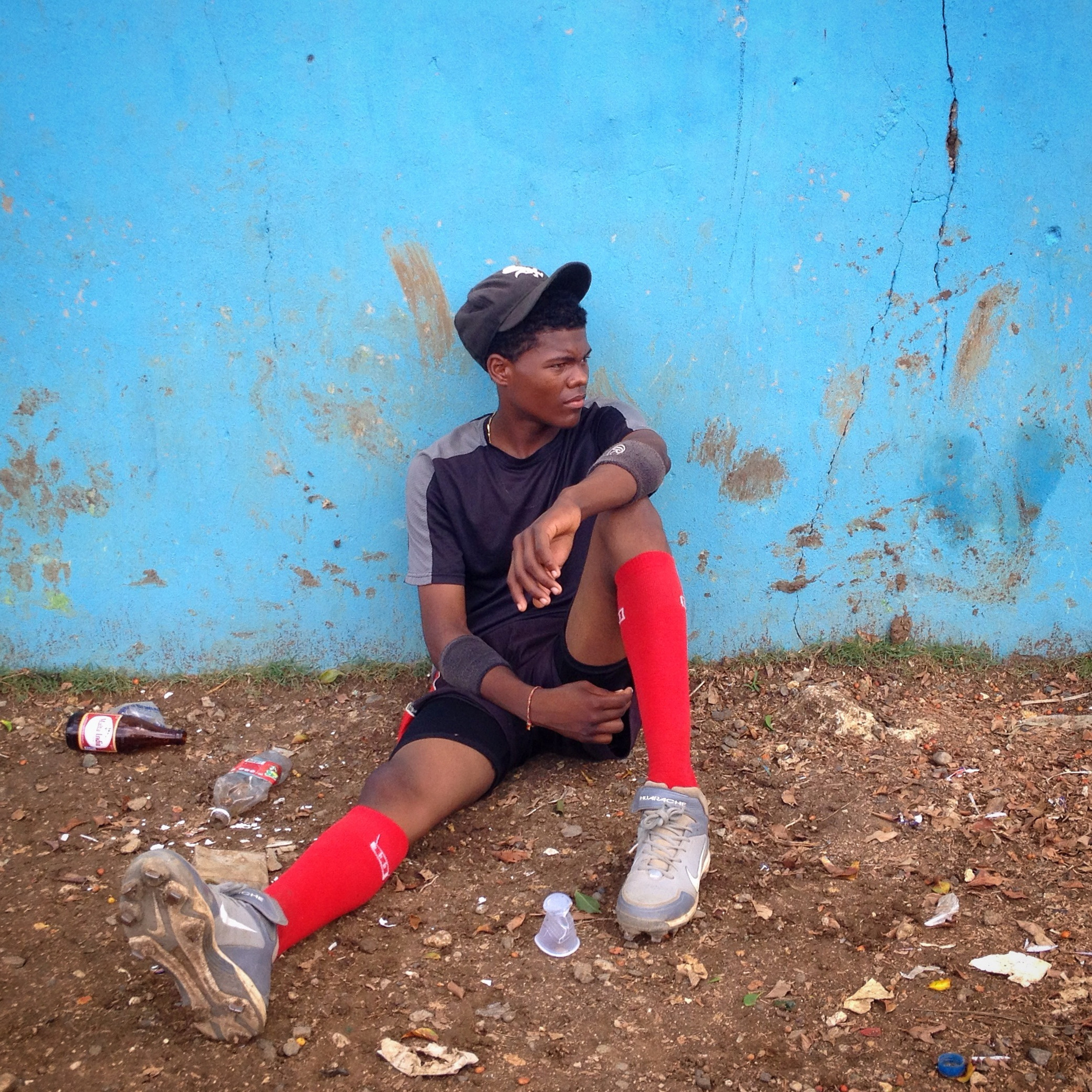 Jean Carlos, 16, rests during practice at the Los Caribe baseball field in the Dominican Republic. He dreams of being an outfielder for the Boston Red Sox. (Tatiana Fernandez Geara)