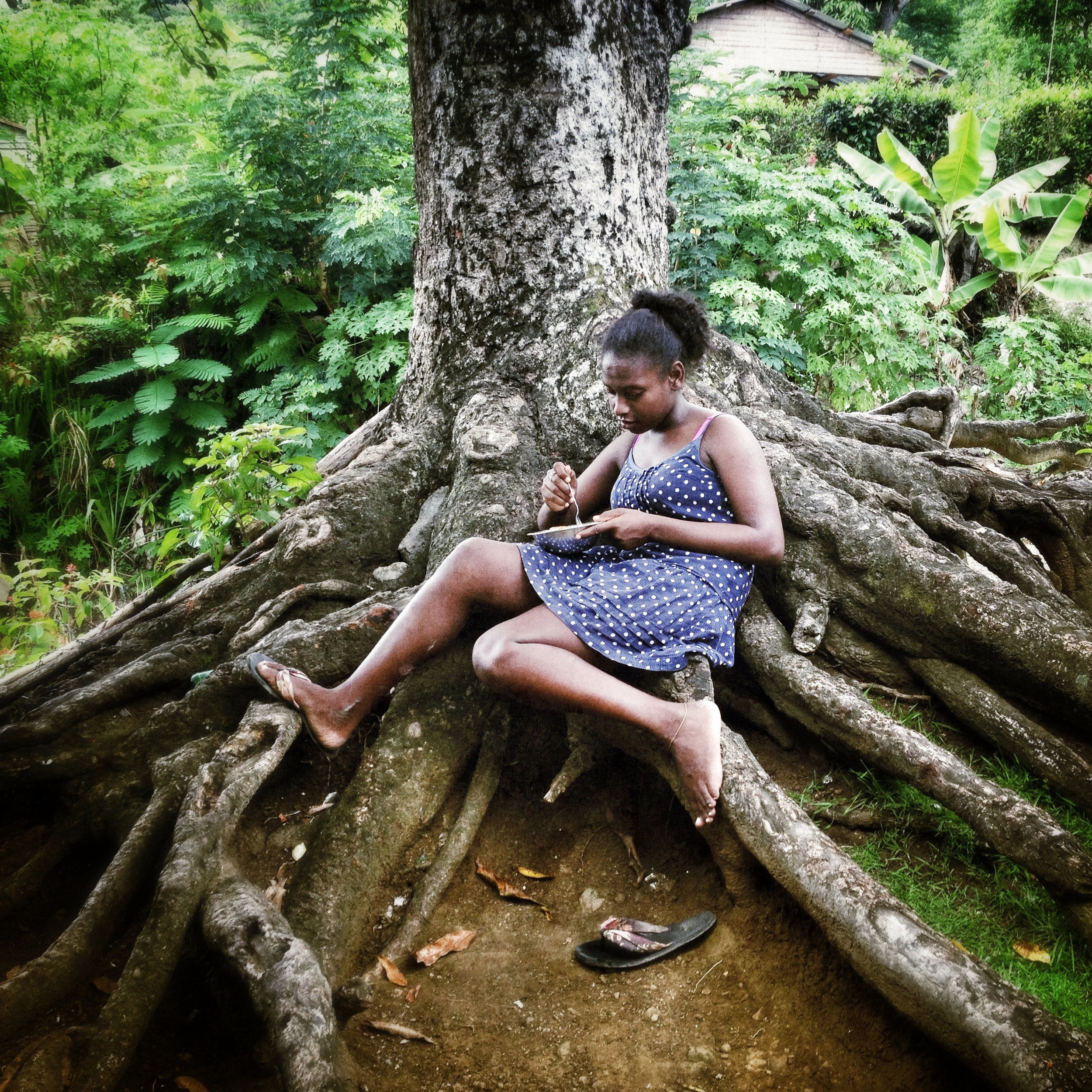 Yessica, 16, has lunch under the mango tree in the patio of her grandmother's house on the last day of her visit in Mucha Agua, San Cristobal, Dominican Republic. She has spent the summer there and is now returning to her mother in another town for the beginning of the school year. (Tatiana Fernandez Geara)
