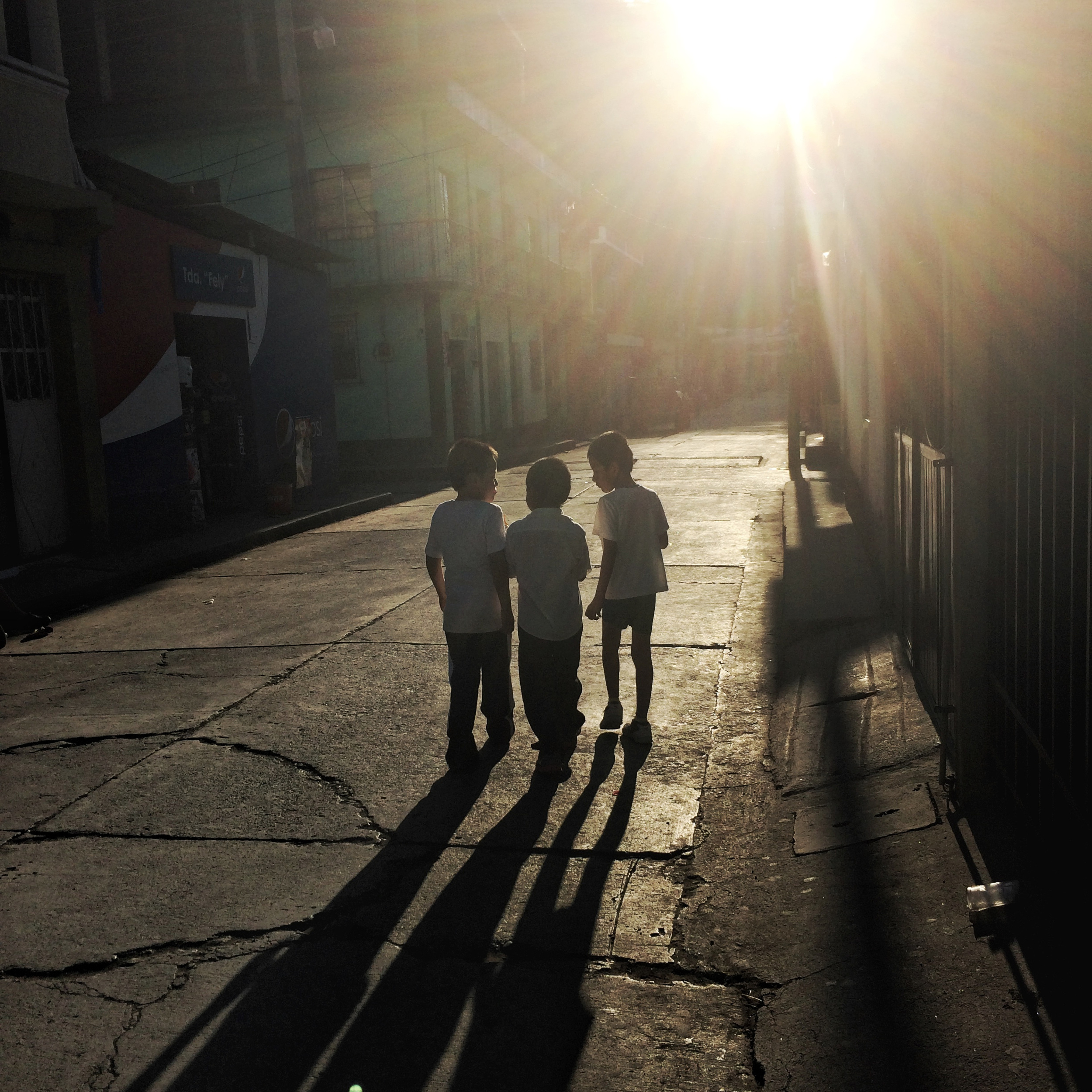 Three boys walk along a street in the late afternoon. Nenton, Huehuetenango, Guatemala. February15, 2016. (James Rodriguez)
