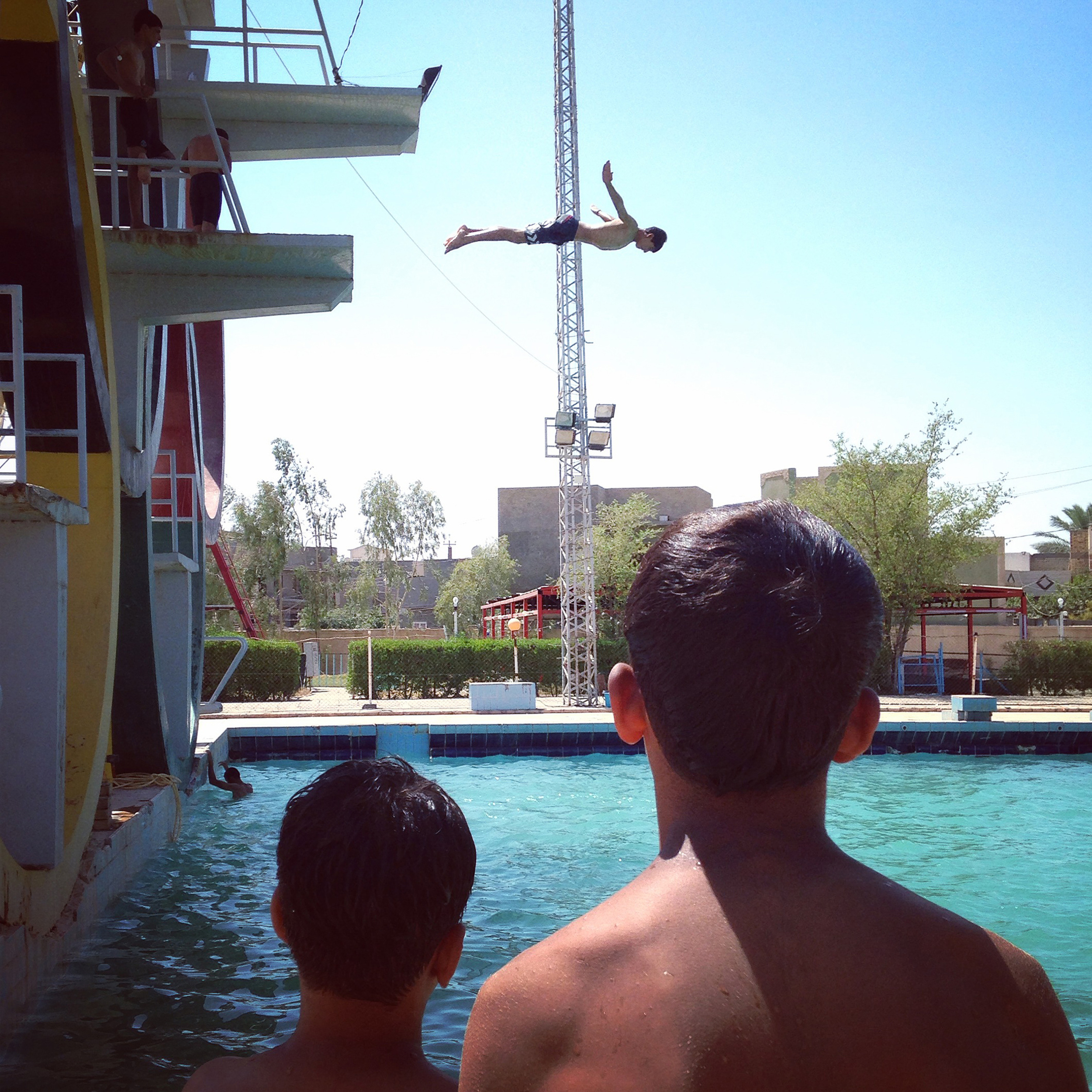 A young man jumps into a public swimming pool during a hot day in the city of Hilla, Babel, Iraq. (Ahmad Mousa)