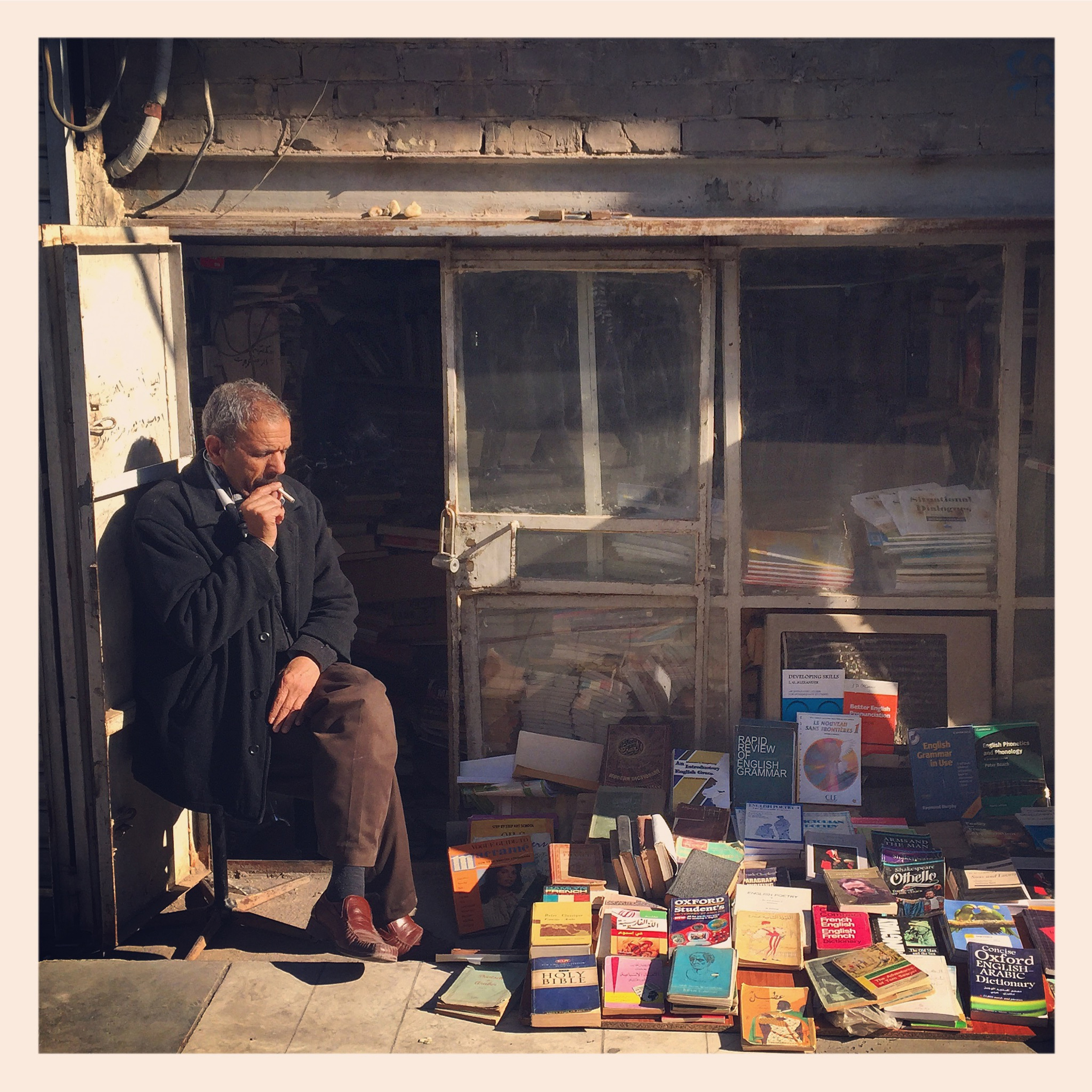 A man sits in front of his book shop on al-Mutanabi street in Baghdad, Iraq. (Ahmad Mousa)