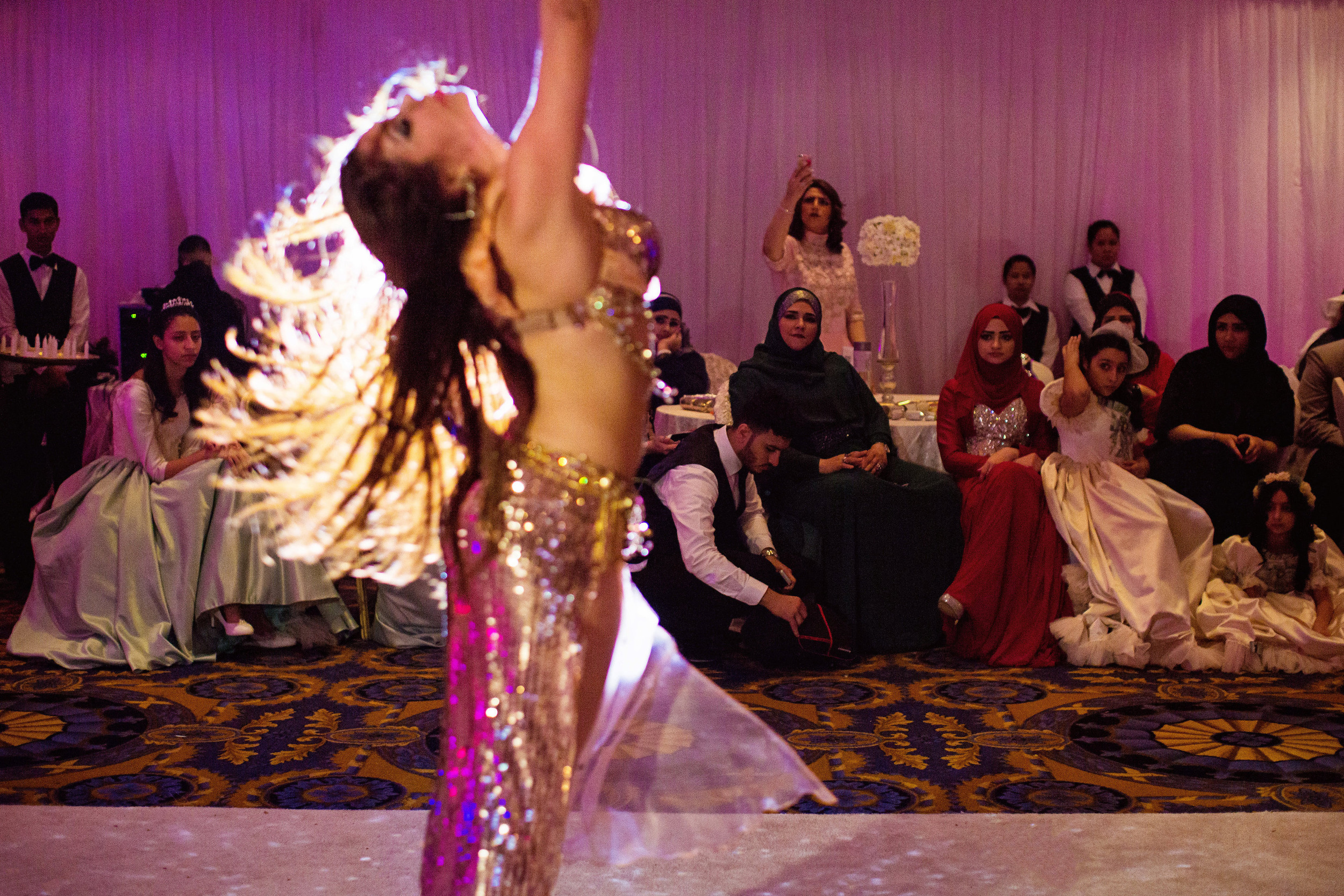 Saudi weddings are gender-segregated by law. Women are able to take off their hijabs and enjoy the night alone and to dress up as they please. Contrary to the Arabian nights stereotype, this is the only wedding I've seen with a belly-dancer. (Tasneem Alsultan)