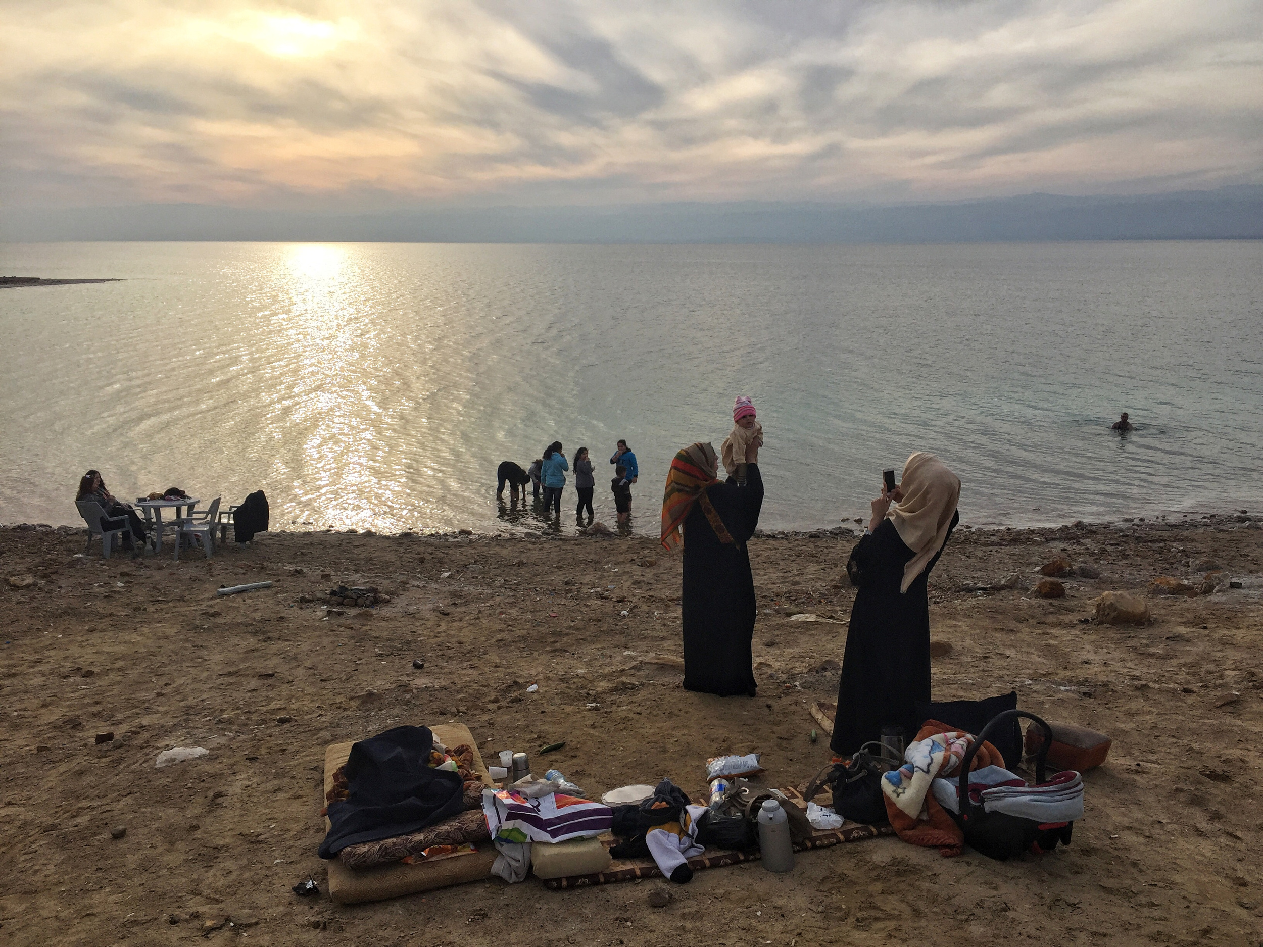 Bathers in the Dead Sea, Jordan. The women sit and enjoy the scene whilst the men float in the water. Usually the men dip in after they've bathed themselves with the natural mud, seeping from the layers of the beach. (Tasneem Alsultan)