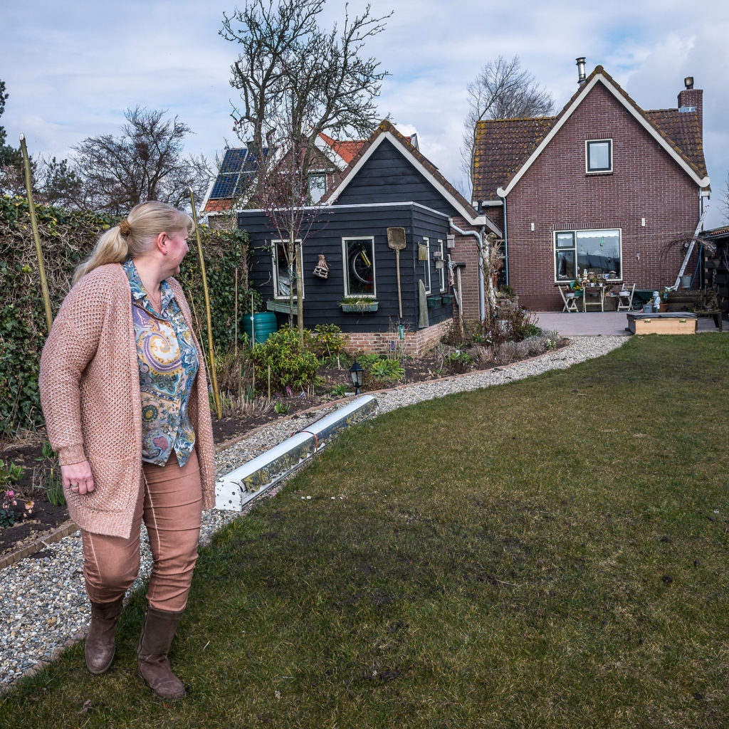 "Anneke van Lelieveld's house sits atop a dike near a ""room for the river"" project in Noordwaard, the Netherlands. She understands the need for a new approach to managing water in this new era of climate change, but misses the neighbors that the project displaced. (Joris van Gennip/The GroundTruth Project)"