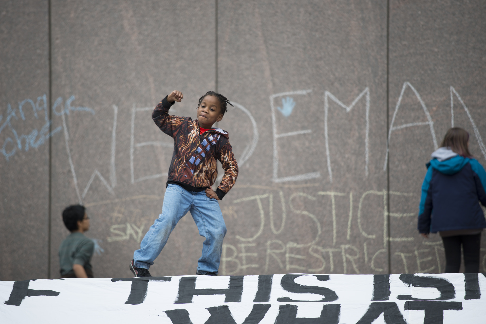 A young boy raises his fist at a protest against the police killing of Jamar Clark in Minneapolis. Shortly after 24-year-old Clark's death, the hashtag #Justice4Jamar started trending on Twitter. (Photo by Fibonacci Blue/Flickr User)