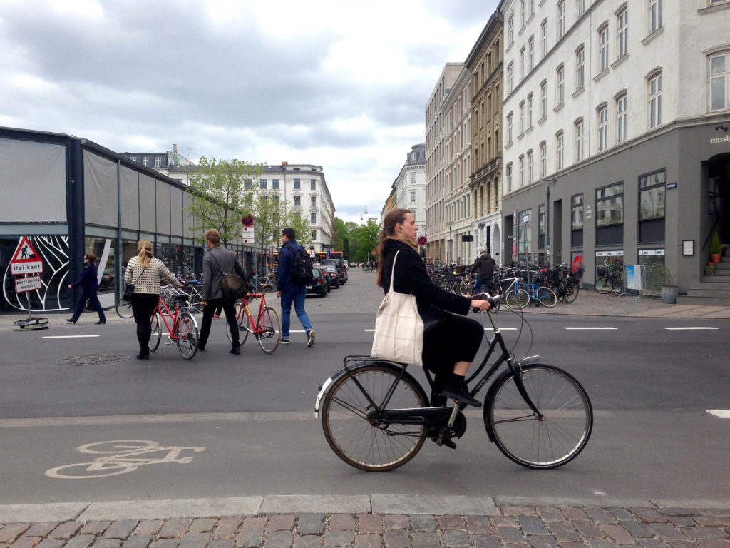 A woman cycles into central Copenhagen. This year, the city ranked first in an index of the world's most bike-friendly cities. (Photo by Charlotte Weiner/GroundTruth)