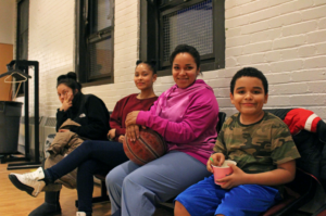 Martinez sitting between her two children, age 14 and 9, with a basketball in her lap. Martinez's daughter and her friend (far left) left the game and returned with a frozen yogurt to share.