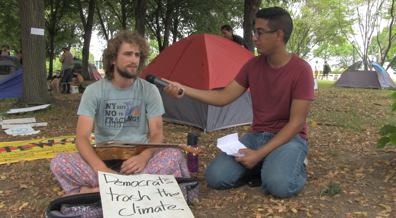 "Tom Moore, a Bernie Sanders supporter, speaks with Abdelfattah. He has a sign in front of him that says ""Democrats trash the climate."" (Photo by Jenny Montasir, GroundTruth)"