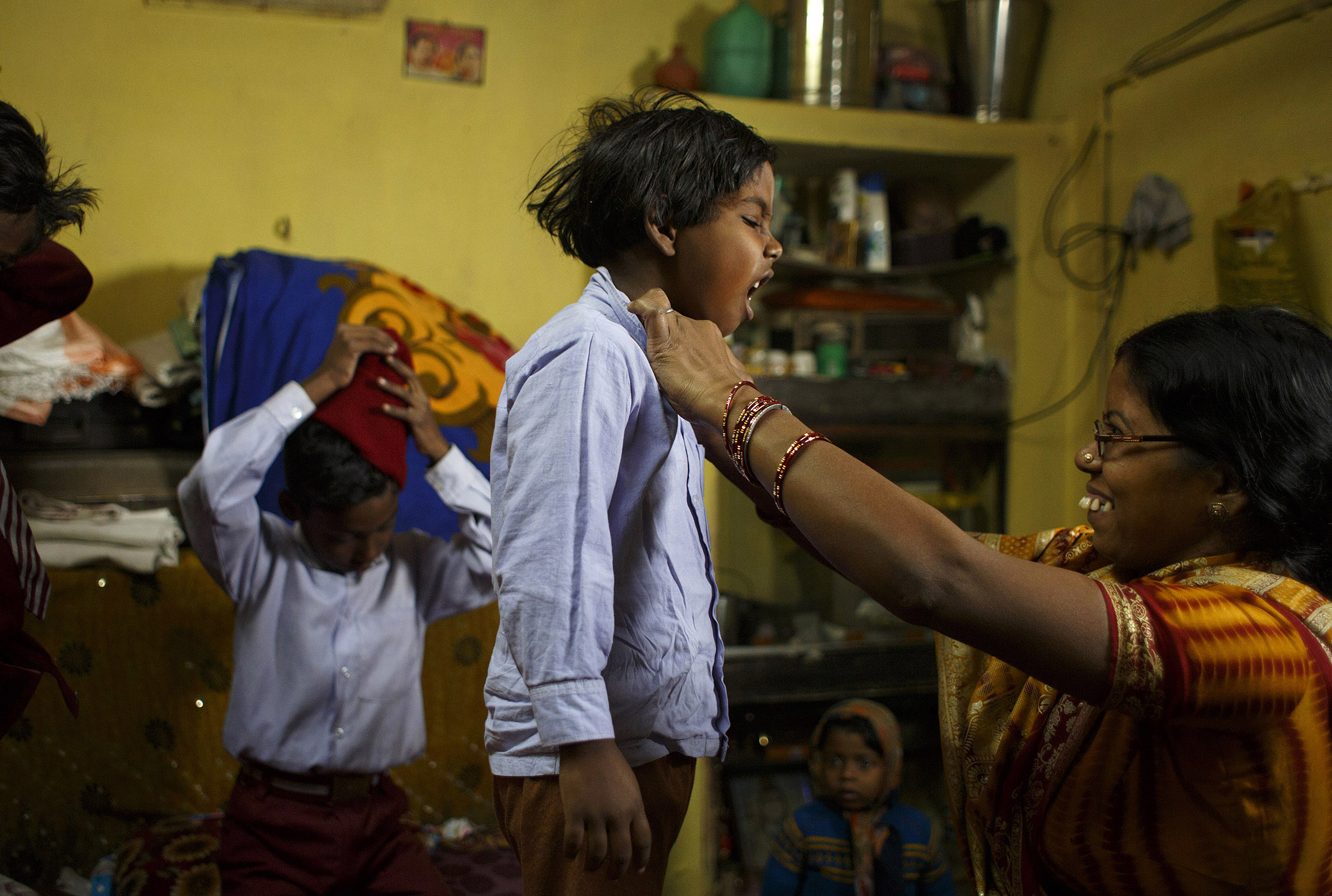Seema Devi, 33, helps her daughter, Semeran Kumari, 6, remove her school uniform after class at their home in Patna, Bihar. Though she came from a large family, she decided her third child would be her last, and after using a Copper-T IUD for years, she chose to get sterilized. She said it would be difficult for her and her husband to support another child, and to provide their three children with the kind of education they want for them.  SARAH WEISER