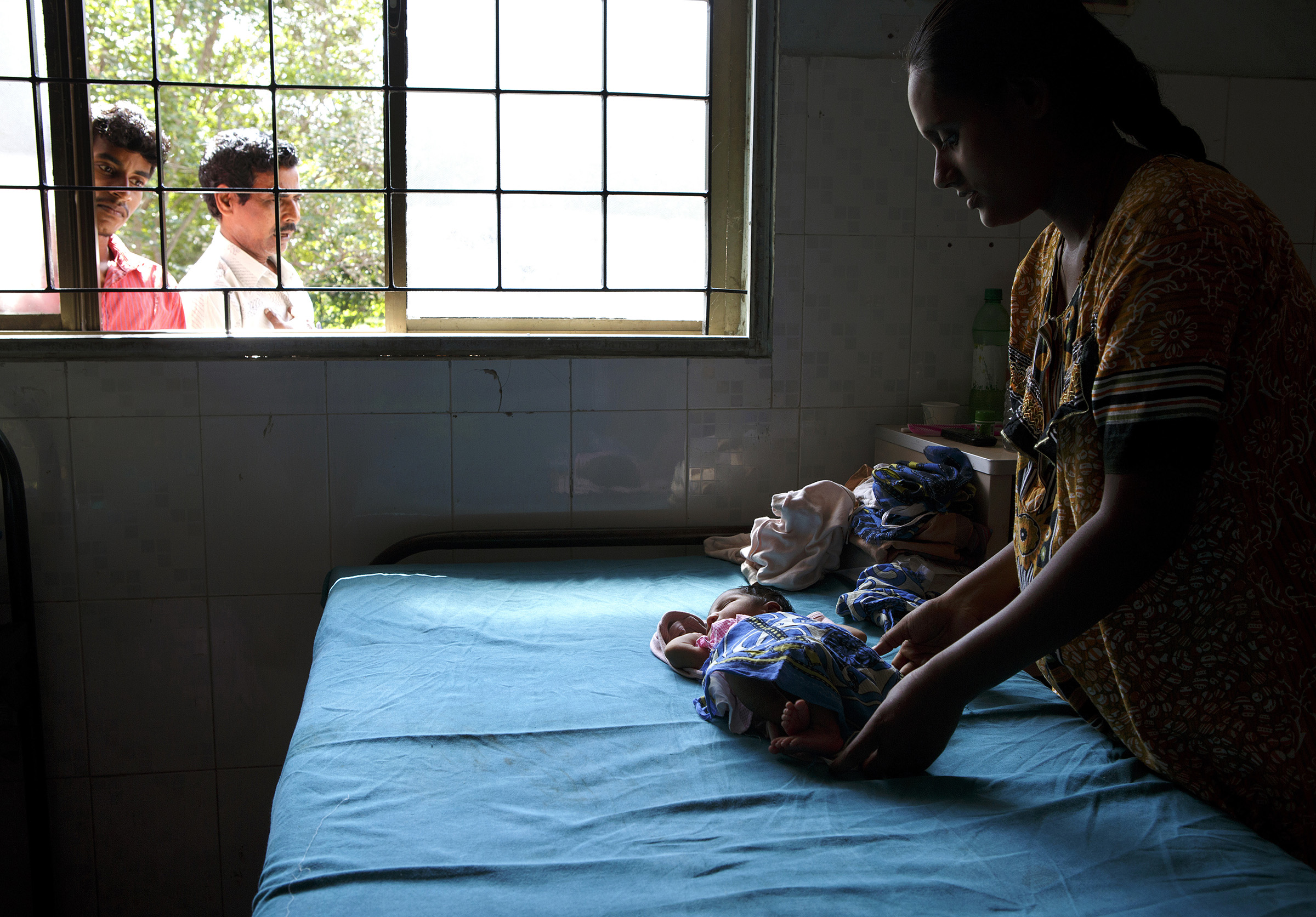 B. Rajeshwari, 23, cares for her first child, a 5-day-old daughter not yet named, at the Medavakkam Primary Health Centre in Tamil Nadu. A family friend, Radish, far left, looks on.   SARAH WEISER